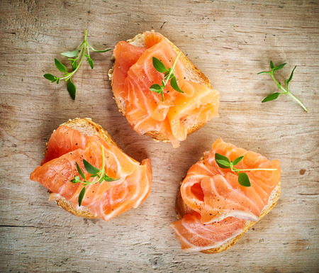 fresh fish: bread slices with fresh salmon fillet on wooden table, top view Stock Photo