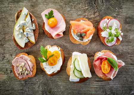 toast: various bruschettas on wooden table, top view