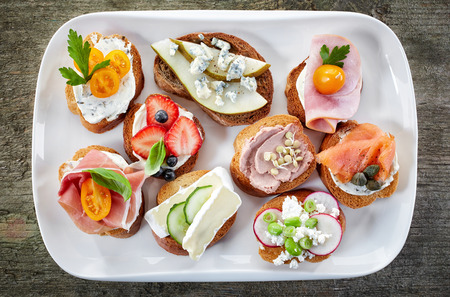 white meat: various bruschettas on wooden table, top view
