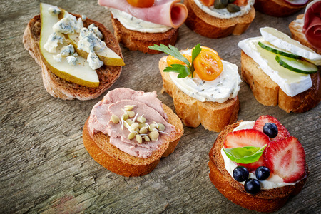 table top: various bruschettas on wooden table, top view