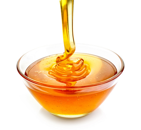 bowl of pouring honey isolated on white background