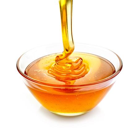 jarabe: tazón de verter la miel aislado en el fondo blanco Foto de archivo