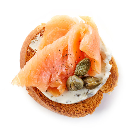 toasted bread slice with smoked salmon and capers isolated on white background, top view Stockfoto