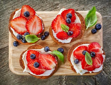 albahaca: rebanadas de pan tostado con bayas y crema de queso