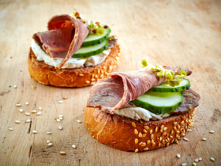 sprouts: toasted bread slices with roast beef and cucumber on wooden table