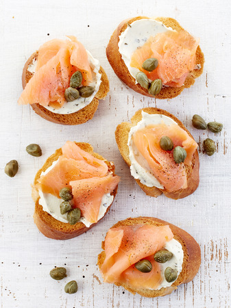 wooden table top view: toasted bread with cream cheese and smoked salmon fillet on wooden table, top view