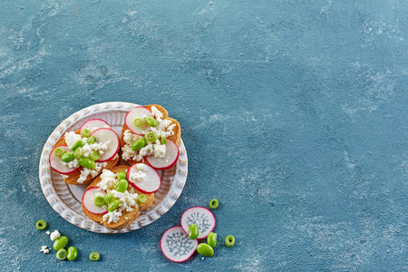 plates of food: toasted bread with radish and cottage cheese on blue background
