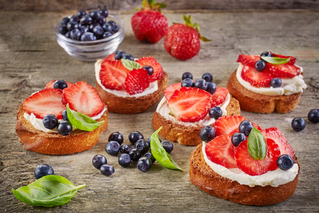 cream cheese: toasted bread with cream cheese and fresh berries on wooden table Stock Photo
