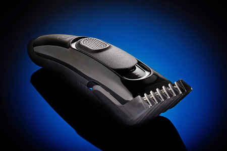 silver hair: hair clipper on a blue background Stock Photo