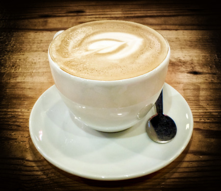 cappuccino cup: cup of cappuccino on wooden table, filtered image
