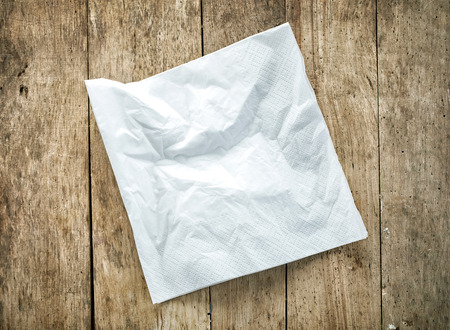 used: white paper napkin on old wooden table Stock Photo
