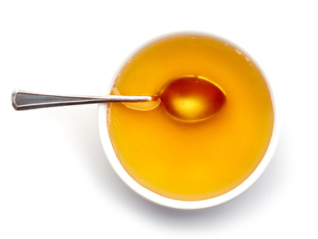 spoon yellow: bowl of honey isolated on white background, top view Stock Photo