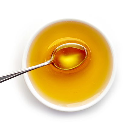 maple syrup: bowl of honey isolated on white background, top view Stock Photo