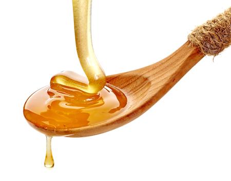 cuchara: cuchara de madera con la miel aislados en fondo blanco Foto de archivo