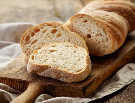 bread slice: freshly baked ciabatta bread on wooden cutting board