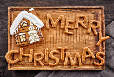 bakery: gingerbread words Merry Christmas and house on wooden cutting board Stock Photo