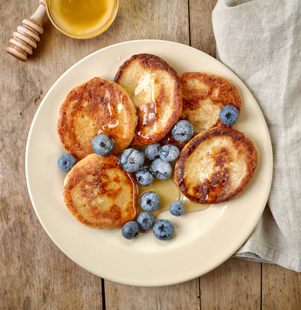 wooden table top view: Pancakes with honey and blueberries on wooden table, top view