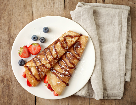 Crepes with strawberries and chocolate sauce Standard-Bild