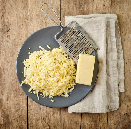 queso: queso rallado en mesa de madera, vista desde arriba Foto de archivo