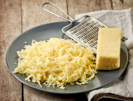 queso rayado: queso rallado en mesa de madera Foto de archivo