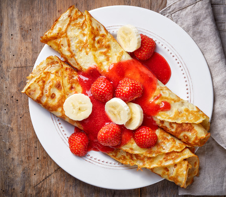 Crepes with strawberries and banana on wooden table, top view