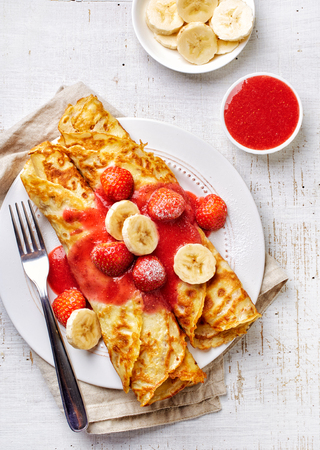 dessert fork: Crepes with strawberries and banana on white wooden table, top view Stock Photo