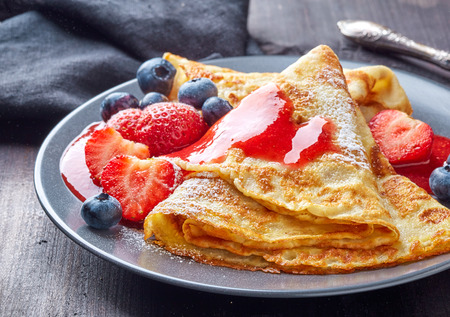 fresh: crepes with fresh berries and sweet sauce on dark wooden table