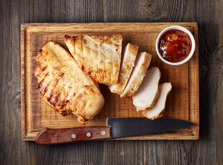 fillets: Grilled chicken fillet on wooden cutting board