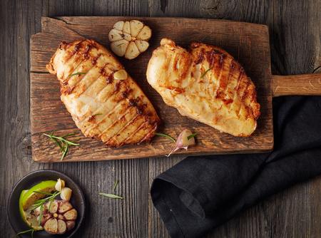 garlic: Filete de pollo a la parrilla en la tabla de cortar de madera Foto de archivo