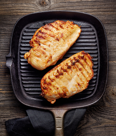 fried food: Grilled chicken fillet on cooking pan Stock Photo
