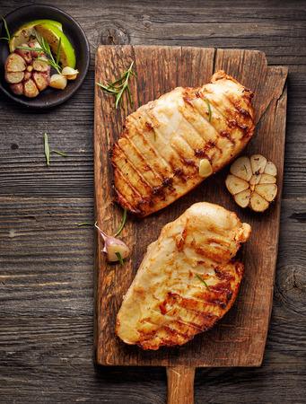 pollo a la brasa: Filete de pollo a la parrilla en la tabla de cortar de madera Foto de archivo