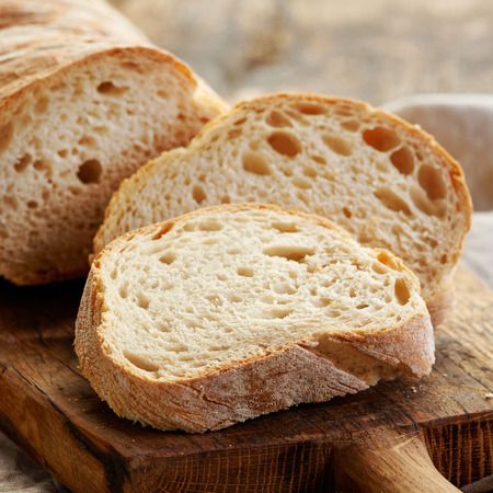 bread: freshly baked ciabatta bread on wooden cutting board