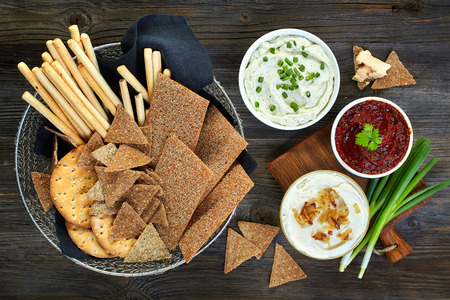various dip sauces and bowl of bread cookies, top view