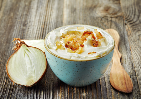 onion: bowl of dip sauce with caramelized onions on wooden table