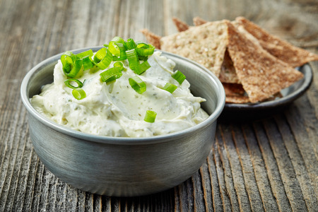 spread: bowl of cream cheese with green onions and herbs, dip sauce on wooden table