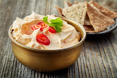 pimenton: tazón de crema de queso con chile y tomate, salsa de inmersión en mesa de madera Foto de archivo