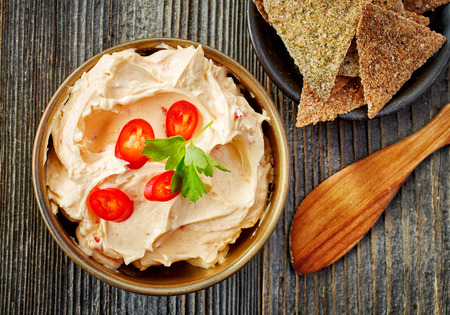 wooden table top view: bowl of cream cheese with chili and paprika, dip sauce on wooden table, top view