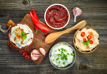 various dip sauces on wooden table, top view Imagens