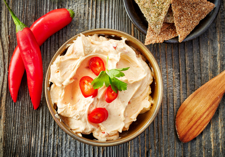 bowl of cream cheese with chili and tomato, dip sauce on wooden table, top view