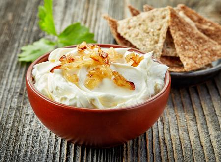 leche: taz�n de crema de queso con cebolla caramelizada en mesa de madera