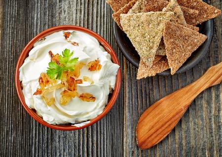 나무 테이블에 캐러멜 양파와 크림 치즈의 그릇, 상위 뷰