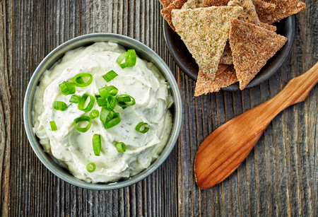 cracker: bowl of cream cheese with green onions and herbs, dip sauce on wooden table, top view