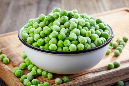 pea: bowl of frozen green peas on wooden table
