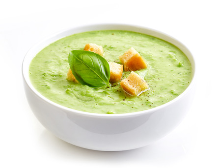 bowl of broccoli and green peas cream soup isolated on white background Stock Photo