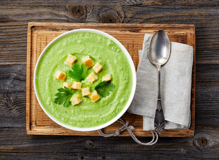 cream and green: bowl of broccoli and green peas cream soup, top view