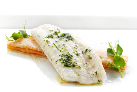 a portion: portion of roasted fish fillet on white plate