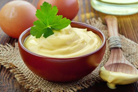 mahonesa: tazón de mayonesa en la mesa de madera