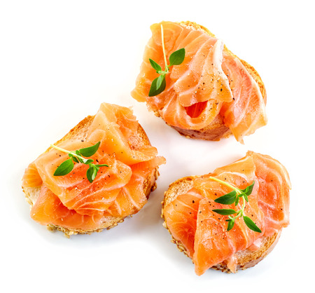 gourmet food: bread with fresh salmon fillet isolated on white background, top view
