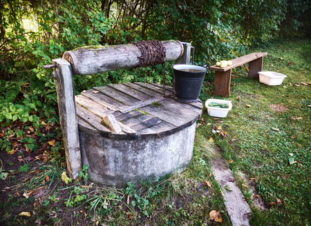 draw well: Rural well with metal bucket Stock Photo