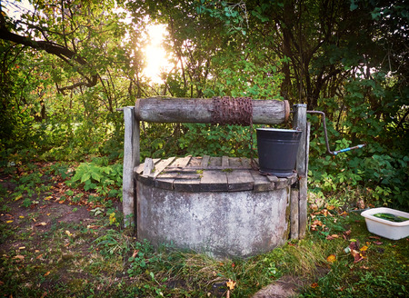 Rural well with metal bucket Stock Photo